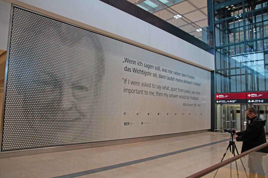 """Der neue Airport der Hauptstadtregion trägt den Namen von Willy Brandt, einem der herausragenden Staatsmänner des 20. Jahrhunderts. Die Gedenkwand zeigt neben dem Konterfei ein Zitat von Willy Brandt: """"Wenn ich sagen soll, was mir neben dem Frieden das Wichtigste sei, dann lautet meine Antwort: Freiheit."""" Außerdem erfahren die Besucher mehr aus dem Leben Willy Brandts und werden über QR-Codes zur Online-Biografie geleitet. Die Gedenkwand befindet sich im öffentlichen Bereich von Terminal 1 auf der Ankunftsebene E0, mittig neben den Treppen zur Check-in-Halle. / Foto: Ingo Paszkowsky"""