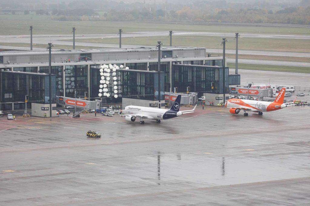 Die am 31. Oktober gelandeten Flugzeuge rollen auf ihre Abfertigungspositionen an den Fluggastbrücken B14 und B15. Im Hintergrund das Kunstobjekt Gadget von Olaf Nicolai, das sich wie ein Armband um die Brücke für den Airbus A380 schlingt / Foto: Thomas Köhler/Photothek